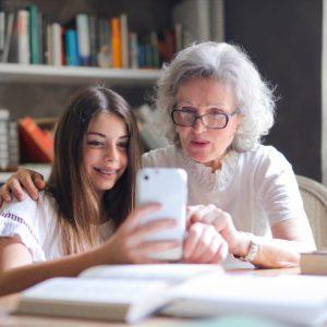 chica joven y mujer mayor con smartphone